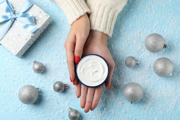 Mulher que guarda o frasco do creme do inverno para a pele, caixa de presente no fundo azul nevado, espaço para o texto.