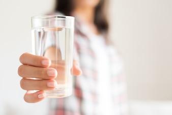 Mulher que guarda o vidro de água potável em sua mão. Conceito de cuidados de saúde.
