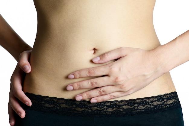Mulher que guarda sua barriga na área da dor isolada no fundo branco.