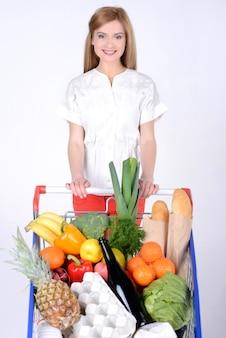 Mulher que guarda um cesto de compras e um carrinho de compras.