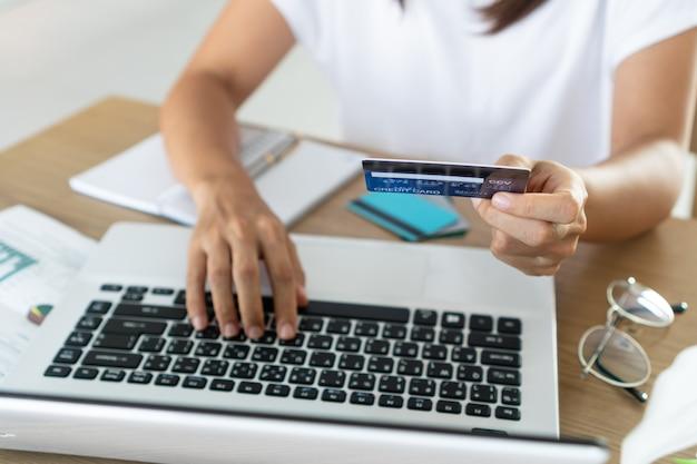 Mulher que guardara o cartão de crédito e que usa o portátil do computador, conta e conceito da economia.