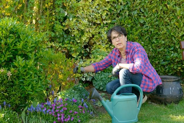 Mulher que jardina as flores em seu jardim bonito.