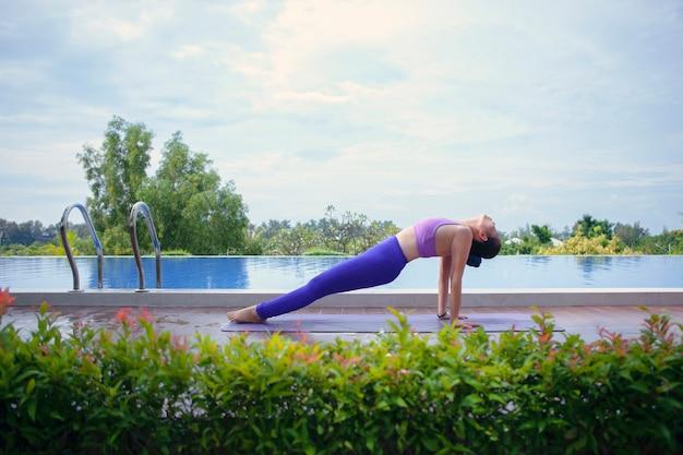 Mulher que joga a pose da ioga ao lado da associação de água do esporte