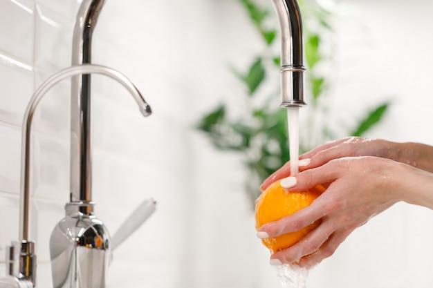 Mulher que lava a laranja madura sob o torneira na cozinha da pia.