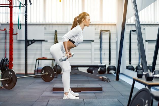 Mulher que levanta um crossfit do peso na ginástica. barra de levantamento terra mulher fitness.