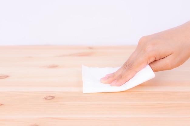Mulher que limpa a tabela de madeira com o lenço de papel.