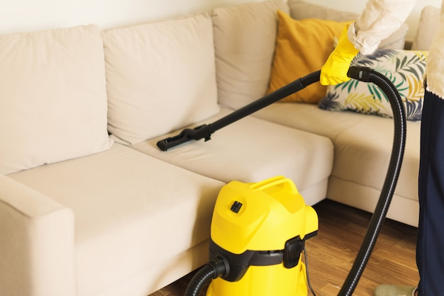Mulher que limpa o sofá com o aspirador de p30 amarelo. conceito limpo