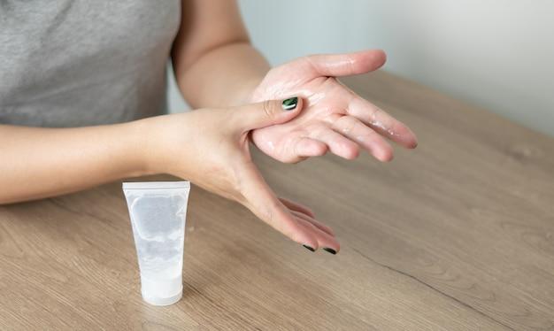 Mulher que limpa seu vírus do desinfetante das mãos e impede o vírus covid-19 que pulveriza o gel do álcool
