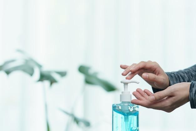 Mulher que limpa suas mãos com o gel antibacteriano líquido do desinfetante, na quarentena, conceito do vírus de corona.