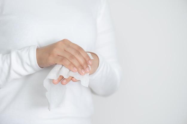 Mulher que limpa suas mãos com tecido molhado ou toalhetes molhados no fundo branco