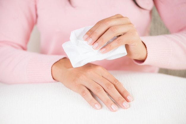 Mulher que limpa suas mãos com um tecido. conceito de saúde e médico