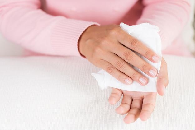 Mulher que limpa suas mãos com um tecido. conceito de saúde.