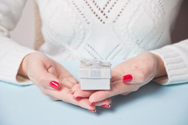 Mulher que mantém uma caixa pequena do goft nas mãos azuis. conceito de compras de natal de inverno