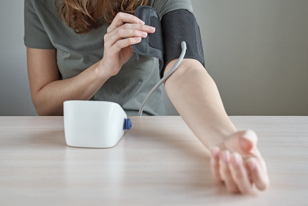 Mulher que mede a pressão sanguínea ela mesma com o monitor digital da pressão. cuidados de saúde e conceito médico