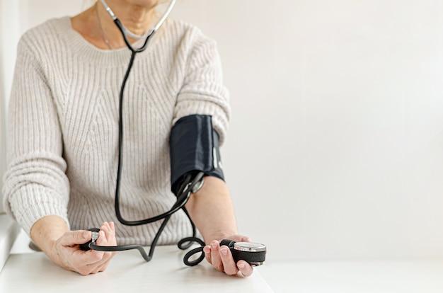 Mulher que mede a pressão sanguínea sozinha em casa com dispositivo manual. auto-cuidado e conceito médico.