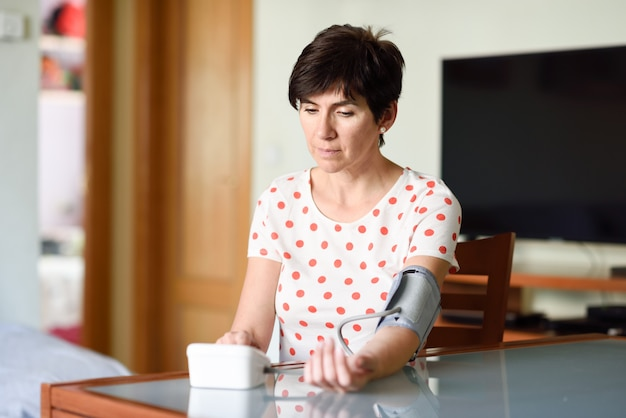 Mulher que mede sua própria pressão sanguínea em casa.
