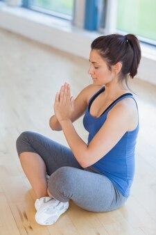Mulher que medita em pose de ioga fácil