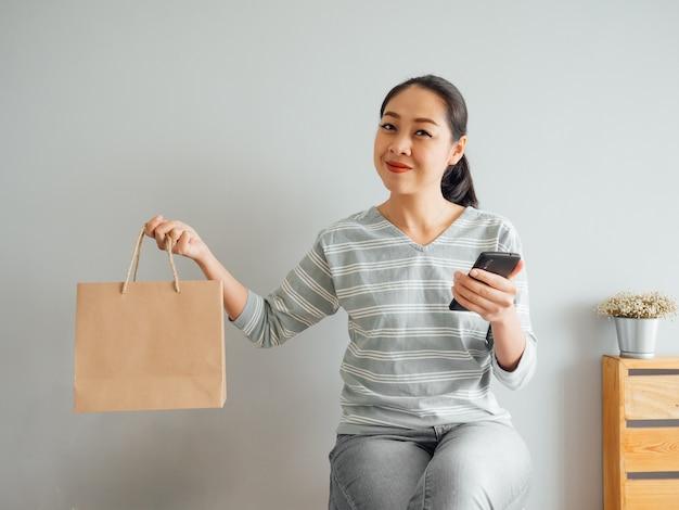 Mulher que mostra fora o saco de papel vazio do produto que comprou em linha.