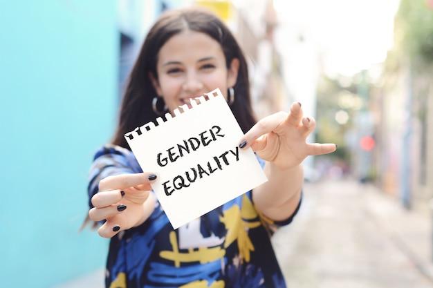 Mulher que mostra um bloco de notas com a igualdade de gênero do texto.