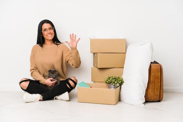 Mulher que move-se para casa no branco que mostra alegre número cinco de sorriso com dedos.