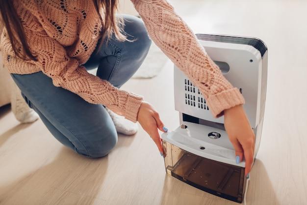 Mulher que muda o recipiente da água do desumidificador em casa. umidade no apartamento. secador de ar moderno