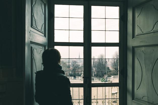 Mulher que olha através da janela, imagem tonificada, estilo do vintage. vista da cidade de turim, torino, itália