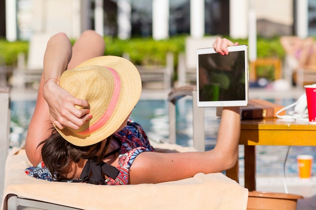 Mulher que olha para um tablet