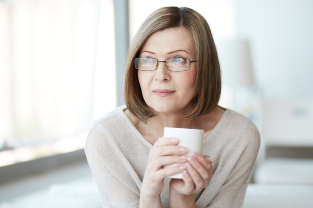 Mulher que pensa com uma xícara de chá