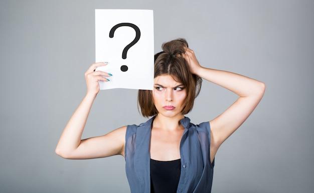 Mulher que pensa. conceito - questão desafiadora, procurando a resposta. menina isolada. mulher com expressão duvidosa e pontos de interrogação. ponto de interrogação, símbolo. pergunta de garota. obtendo respostas, pensando.