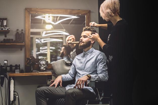 Mulher que penteia o cliente na barbearia