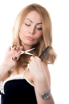 Mulher que penteia seu cabelo e tesouras