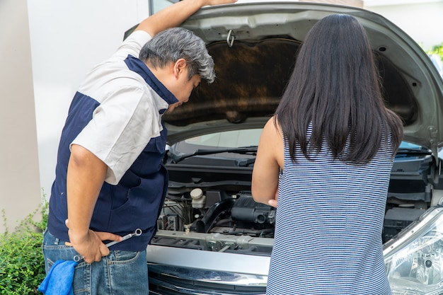 Mulher que possui o carro parado e procurando por mecânico de automóveis verifique o motor para encontrar a causa.