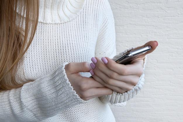 Mulher que prende o telefone móvel moderno na luz de fundo.