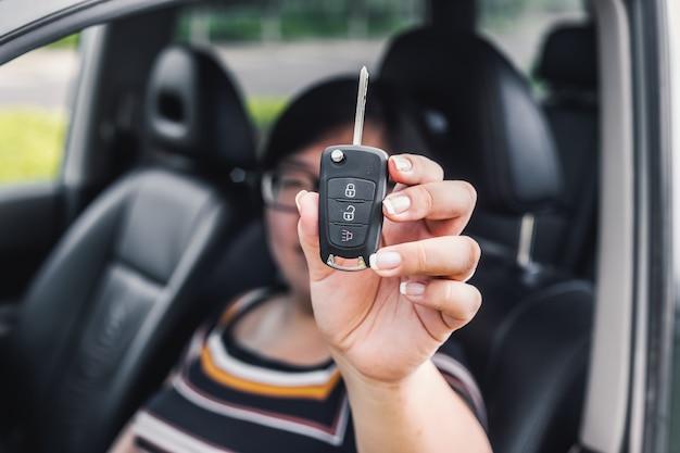 Mulher que prende uma chave do carro