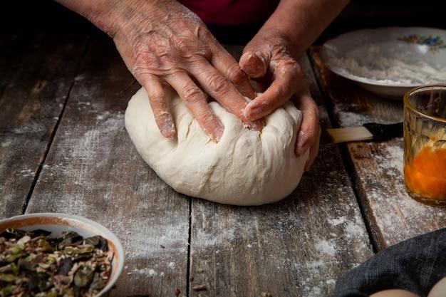 Mulher que prepara a massa em close-up de madeira mesa.