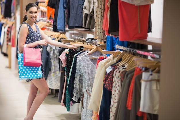 Mulher que procura pelo trilho da roupa enquanto segura dois sacos