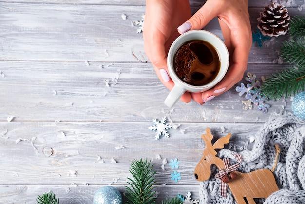 Mulher que realiza nas mãos café quente do natal contra decorações, cervos de madeira, cones, neve, brinquedos do natal na placa de madeira.