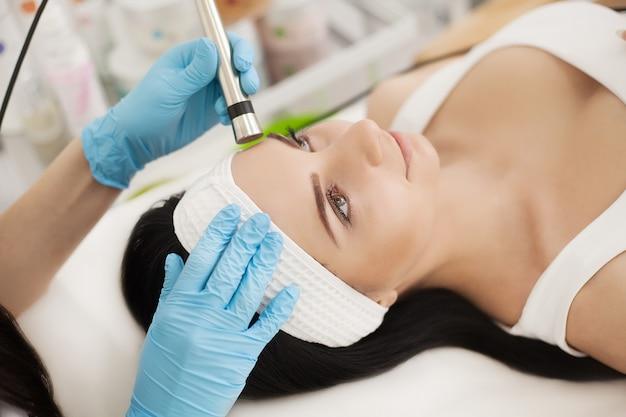 Mulher que recebe a análise de pele da cara.