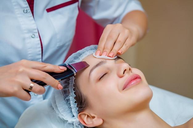 Mulher que recebe a esfoliação facial ultra-sônica no salão da cosmetologia.