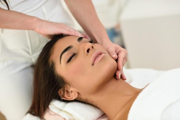 Mulher que recebe a massagem principal no centro do wellness dos termas.