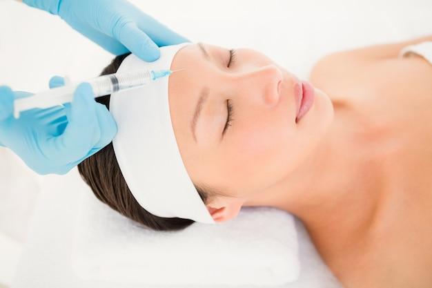 Mulher que recebe injeção de botox em sua testa