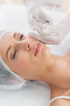 Mulher que recebe injeção de botox nos lábios