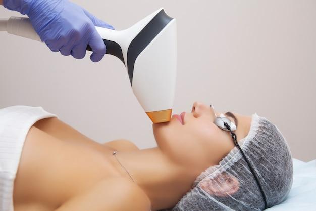 Mulher que recebe o tratamento facial da beleza, removendo a pigmentação na clínica cosmética.