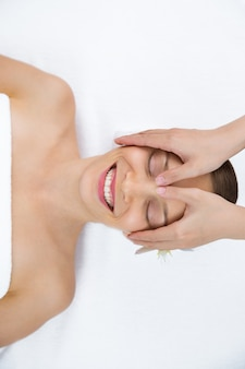 Mulher que recebe uma massagem no rosto