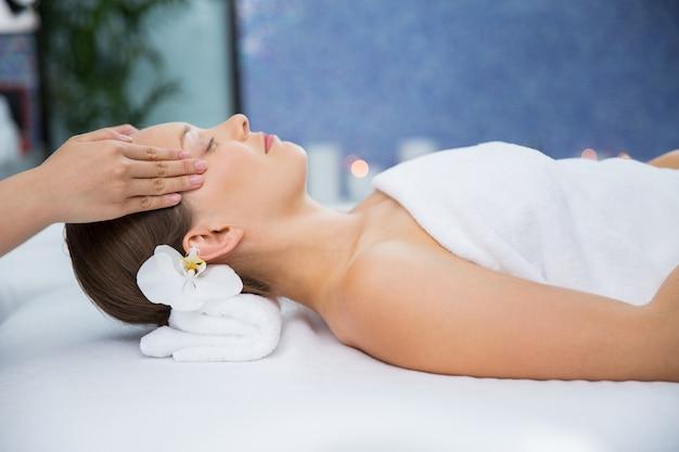Mulher que recebe uma massagem nos templos