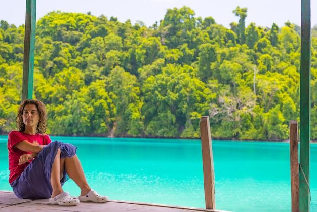 Mulher que relaxa na estância turística no mar colorido das ilhas remotas de togean, sulawesi, indonésia.