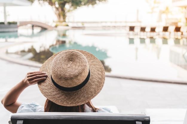 Mulher que relaxa no hotel de luxo bonito perto da piscina, conceito das férias de verão.