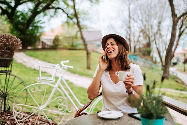 Mulher que ri ao falar no telefone no café.