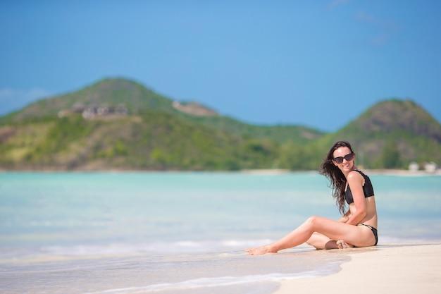 Mulher que senta-se na praia que ri e que aprecia as férias de verão que olham a câmera. modelo bonito no biquini que senta-se para baixo.