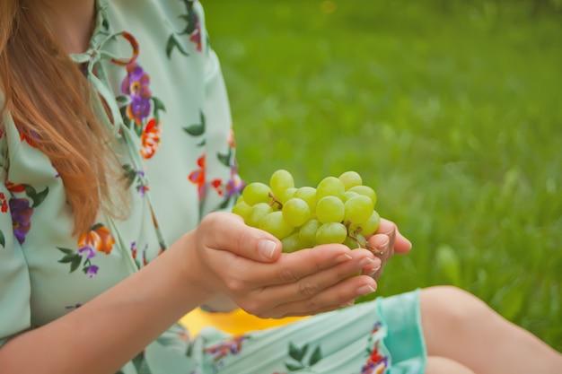 Mulher que senta-se na tampa amarela e que guarda o grupo de uvas.